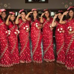 All in red dresses holding red and white flowers
